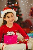 Festive little girl smiling at camera with gifts against snow falling
