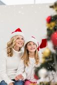 Festive mother and daughter smiling at tree against twinkling stars