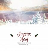 Joyeux noel against snowy landscape with fir trees