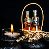 Aromatic Spa Concept Of Bottles Essential Oil In Basket, Dried Lavenders And Candles On Black Zen Ba