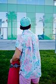 Stylish hipster man with copy space cup on the head, young stylish man in bright summer clothes