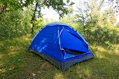 Blue Tourist tent on summer meadow
