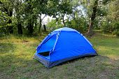 Blue tourist tent in forest camp