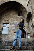 Attractive tourist girl on vacation with a map in antique gothic city