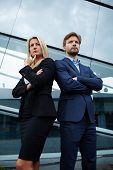 Confident business team of man and woman standing with crossed hands team spirit concept