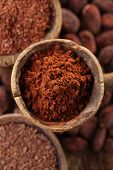 image of chocolate spoon  - cocoa powder in spoon on roasted cocoa chocolate beans background - JPG