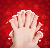 Fingers Faces In Santa Hats Against Red Snowflakes Background. Concept For Christmas Or New Years Da