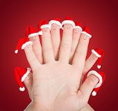 Fingers Faces In Santa Hats Against Red Background. Concept For Christmas Or New Years Day