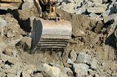 foto of track-hoe  - Tracked excavator or track hoe digging at a large construction site removing a hill - JPG