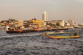 picture of barge  - a thai longtail boat and a big barge over the bangkok skyline seen from the Chao Phraya river - JPG