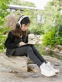 Young Girl Reading Book And Listen To Music In Park
