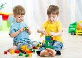 foto of daycare  - Kids boys play toys in playroom at nursery - JPG