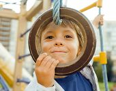 foto of playground  - little cute boy hanging on gymnastic ring at playground outside - JPG