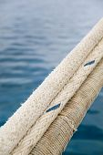 stock photo of dock  - Heavy duty and weathered ropes attached to the pier for secure docking of a ship - JPG