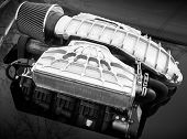 pic of combustion  - Outer supercharger air compressor that increases the pressure or density of air supplied to an internal combustion car engine mounted on a hood monochrome photo with selective focus and shallow DOF - JPG