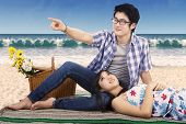 stock photo of couple sitting beach  - Attractive young couple enjoy holiday while sitting on mat at beach and looking at something - JPG