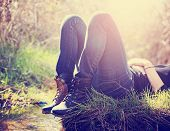 picture of boot  - a girl lying on a small island in a stream with jeans and black combat boots on backlit with the setting sun toned with a retro vintage instagram filter effect app or action  - JPG