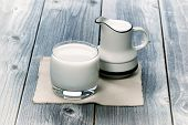 stock photo of pitcher  - Vintage concept of a glass of milk and pitcher on rustic wood - JPG