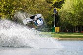 pic of ponds  - Male wakeboarder jumps over spray on pond in park - JPG
