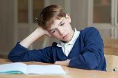 picture of diligent  - Diligent school teen sitting at desk classroom - JPG