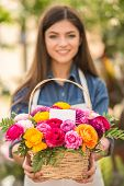 picture of bouquet  - Young female florist holding bouquet of flowers in shop - JPG