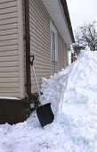 foto of snow shovel  - Clearing large drifts of snow shovel near the house - JPG