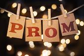 picture of glow  - The word PROM printed on clothespin clipped cards in front of defocused glowing lights - JPG