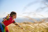 pic of hay fever  - Cute little girl picking and gathering brown grasses on a meadow with the wind blowing through her long hair and sea in the background - JPG