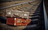 stock photo of old suitcase  - The image of two old forgotten suitcases on railway tracks - JPG