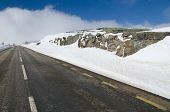 foto of icy road  - Mountain road with white snow and blue cloudy sky - JPG