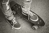 picture of skate board  - Young skateboarder in gumshoes and jeans standing on his skate - JPG