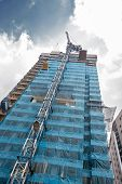 stock photo of scaffold  - crane at work on scaffold of tall building - JPG