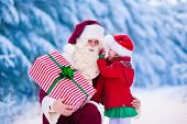 Постер, плакат: Santa Claus Talking To Little Girl In Snowy Park