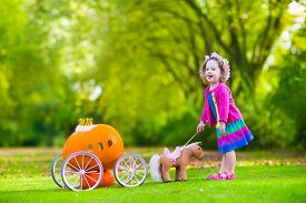 foto of cinderella  - Cute curly little girl playing Cinderella fairy tale holding magic wand next to a pumpkin carriage in autumn park at Halloween - JPG