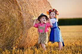 stock photo of pretzels  - Kids in traditional Bavarian costumes in wheat field - JPG