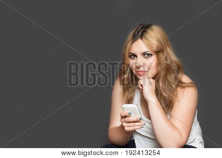Studio shot of attractive long haired teenage girl holding her smart phone and looking at the camera. All is on the gray background. All potential trademarks and buttons are removed.