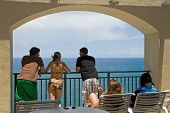 foto of spring break  - Young people talk and relax on a balcony under an arch overlooking the ocean - JPG