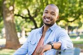 Young african man relaxing at park in a summer day. Happy black cheerful guy feeling good and sittin poster