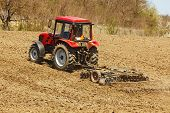 pic of cultivator-harrow  - Red tractor on hill with disk harrow and rake - JPG