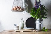 Concept Of Rural Kitchen. Lupines In A Can, Milk, Eggs And Ware On A Wooden Table Against The Backgr poster