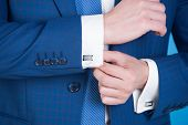 Hand Fixing Elegant Cufflink On White Shirt Cuff Sleeve poster