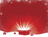 Red Christmas box with light explosion on snowy background