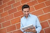 Attractive man using electronic tablet leant on brickwall