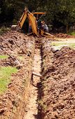 stock photo of backhoe  - A backhoe rests after digging the ditch - JPG