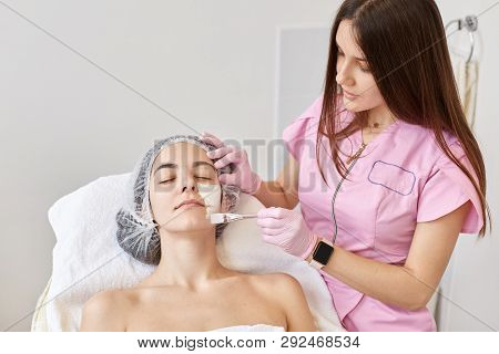 poster of Cosmetologist Applys Peeling Mask To Her Client Face. Woman Getting Facial Care By Beautician At Spa