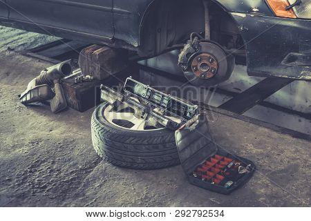 poster of Car Brake Repairing In Garage, Brakes On A Car With Removed Wheel, Car Brake Part At Garage, Car Bra