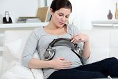 Pregnant woman putting headphones on her belly