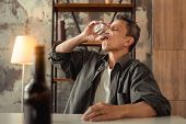 Shabby Adult Man Emptying Glass Of Alcohol With One Sip poster