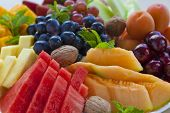 picture of fruit platter  - Colorful summer fruit platter with watermelon cantaloupe grapes cherries apricots pineapples walnuts and mint - JPG