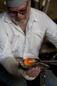 Glass blower shaping molten glass